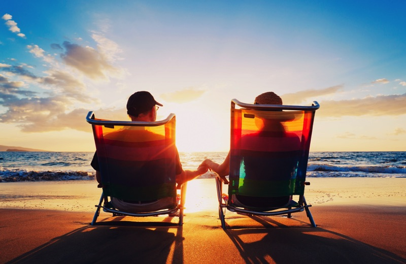 Old couple holding hands sitting on deck chairs